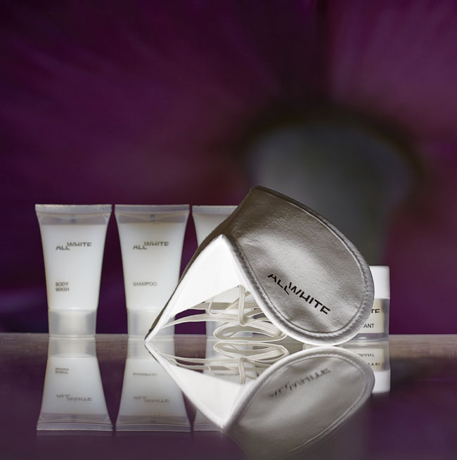 All White guest amenities showing three semi-transparent bottles and caps containing bath conditioner, shampoo and body wash, semi-transparent jar with glossy white lid and a white cotton sleeping mask - graphics by Bonnelycke mdd
