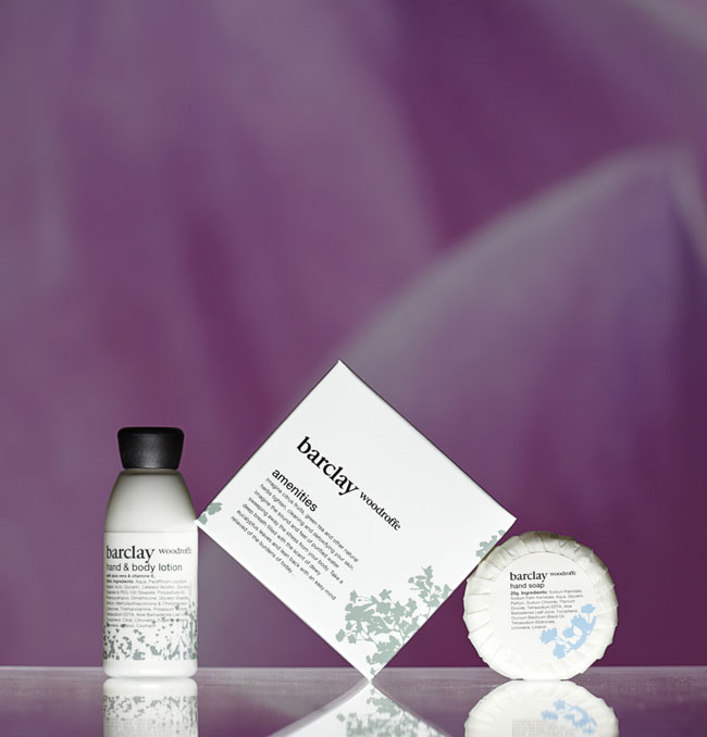 Barclay Woodroffe guest amenities showing a labelled transparent cylindrical bottle with black cap containing lotion, a glossy white square paper box, and a pleat wrapped soap bar sealed by a round label - graphic by Bonnelycke mdd