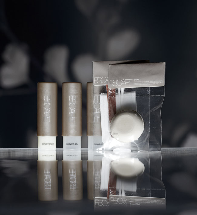 Escape guest amenities showing three semi-transparent cylindrical bottles covered 3/4 by coloured brown cylindrical caps containing conditioner, shower gel and shampoo and two labelled transparent rectangular bags containing vanity kit and soap bar - graphic by Bonnelycke mdd