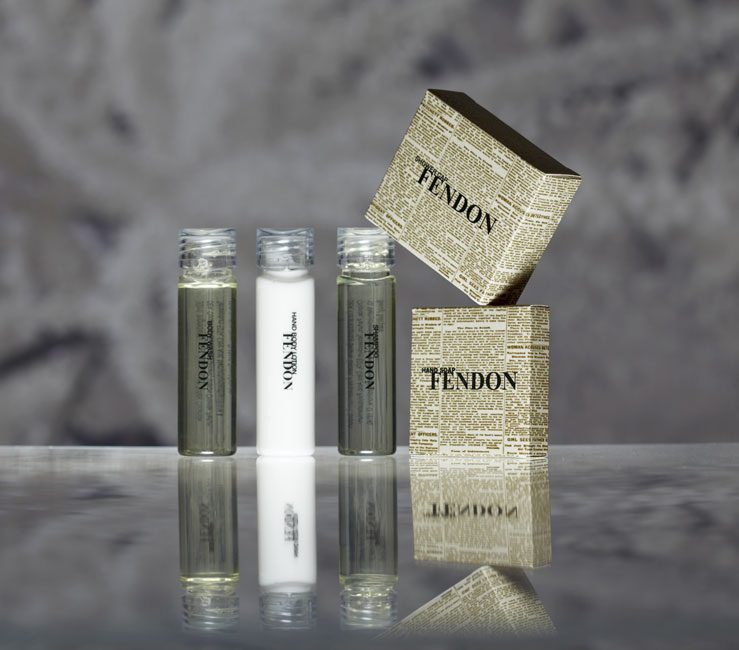 Fendon guest amenities showing three transparent cylindrical bottles with transparent caps containing body wash, lotion and shampoo, and two rectangular paper boxes containing shower cap and soap bar - graphic by Bonnelycke mdd