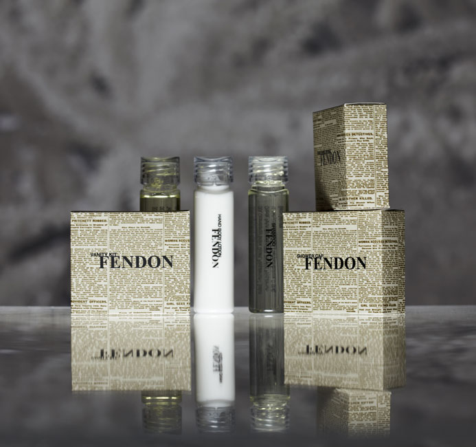 Fendon guest amenities showing three transparent cylindric bottles with transparent caps containing body wash, lotion and shampoo and three rectangular paper boxes containing vanity kit, shower cap and soap bar - graphic by Bonnelycke mdd
