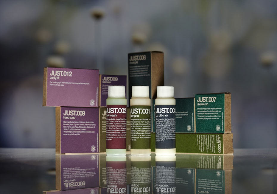 Just fully biodegradable guest amenities showing three plastarch material cylindric bottles containing body wash, shampoo and conditioner, and rectangular and square brown paper boxes with soy ink print containing various amenities - graphics by Bonnelycke mdd