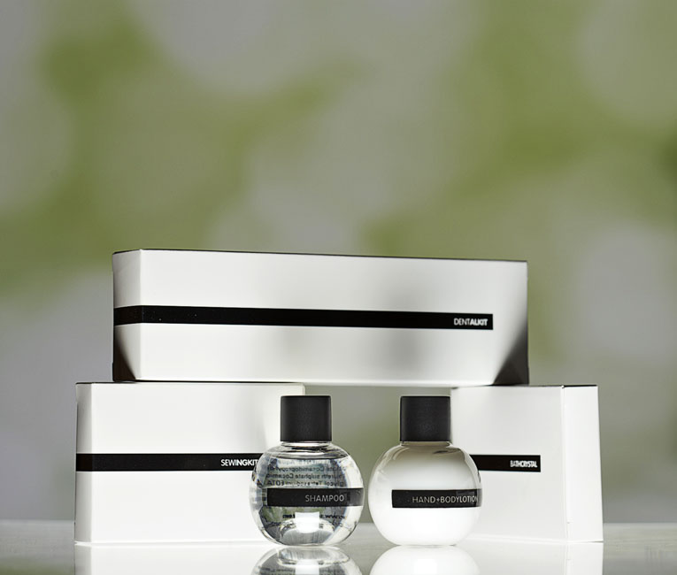 Mini Ball guest amenities showing three glossy rectangular white paper boxes containing dental kit, sewing kit and bath crystals, and two transparent ball shaped bottles with black caps containing shampoo and lotion - graphics by Bonnelycke mdd