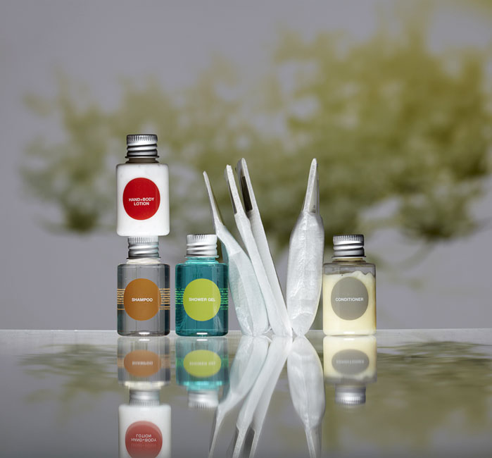 More guest amenities showing four transparent cylindrical bottles with metal caps containing lotion, shampoo, shower gel and conditioner, and four labelled rectangular foam bags containing shower cap, soap, cotton buds and nail files - graphics by Bonnelycke mdd