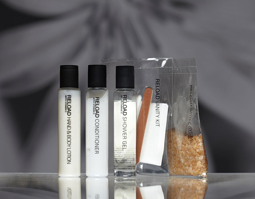 Reload guest amenities showing three transparent cylindrical bottles with black caps containing lotion, conditioner and shower gel, two transparent rectangular heat sealed bags with vanity kit and bath crystal - graphics by Bonnelycke mdd
