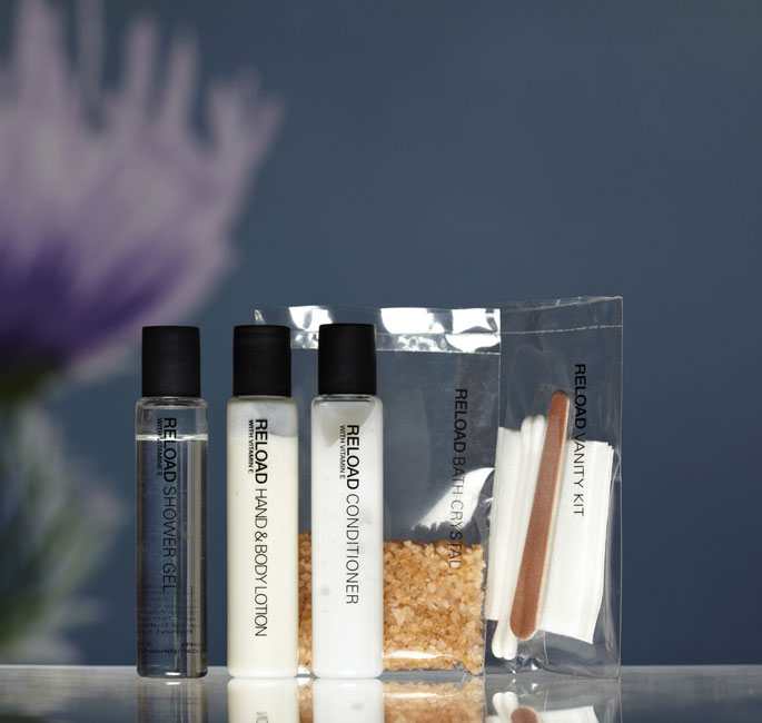 Reload Guest Amenities showing three transparent cylindrical bottles with black caps containing shower gel, lotion and conditioner, transparent rectangular heat sealed bags containing bath crystal and vanity kit - graphic by Bonnelycke mdd