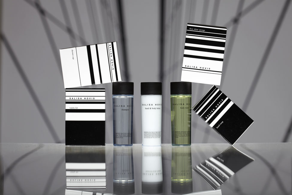 Salisa Hovis guest amenities showing three transparent conic plastic bottles with black caps containing shampoo, lotion and body wash, and four glossy white rectangular boxes containing shower cap, vanity kit, shoe shine sponge and hand soap - graphics by Bonnelycke mdd
