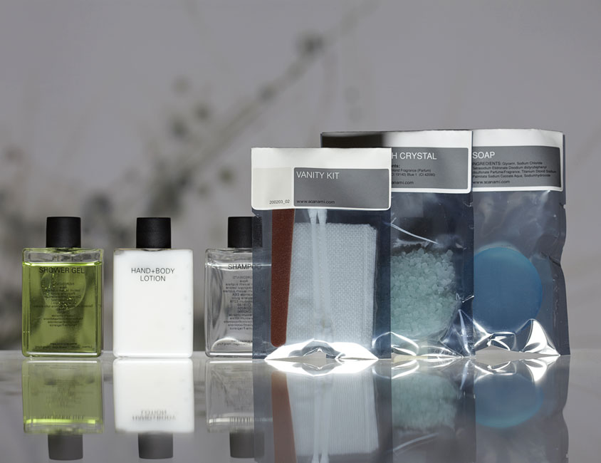 Square guest amenities showing three transparent plastic rectangular bottles with black caps containing shower gel, lotion and shampoo, and three labelled rectangular metallic bags containing vanity kit, bath crystals and soap - graphics by Bonnelycke mdd