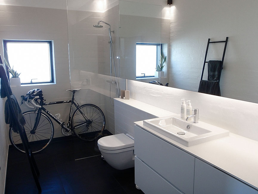 Bonnelycke mdd interior designed all white bathroom in private home with a racing bike in the shower cabinet and a black ladder with black towels.