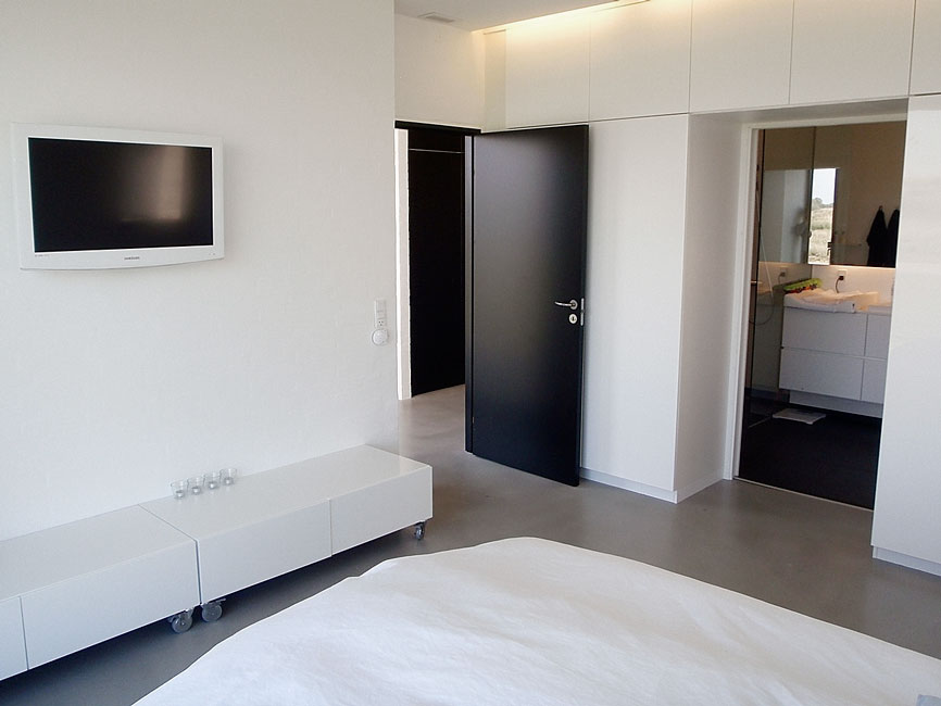 Bonnelycke mdd interior designed bedroom in private home with modern white furniture and integrated white cabinet wall.