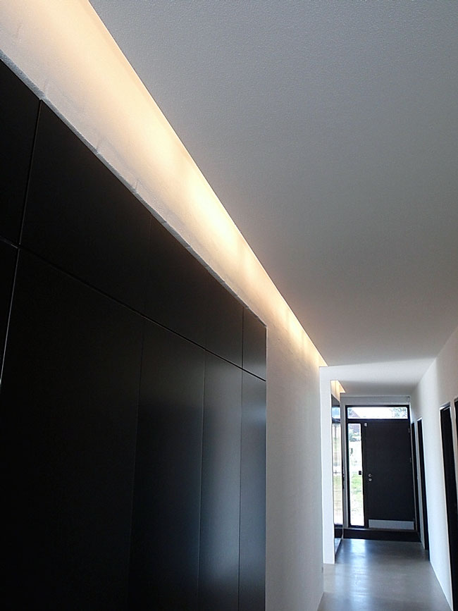 Bonnelycke mdd interior designed private home with black integrated cabinets in a very long white hallway with hidden light along the ceiling.