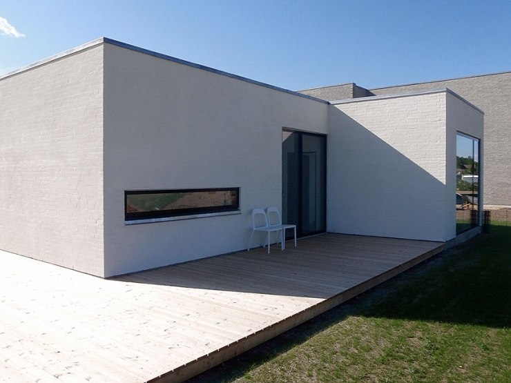 Bonnelycke mdd architectural designed white painted brick private home with black window and door frames and wooden terrace.