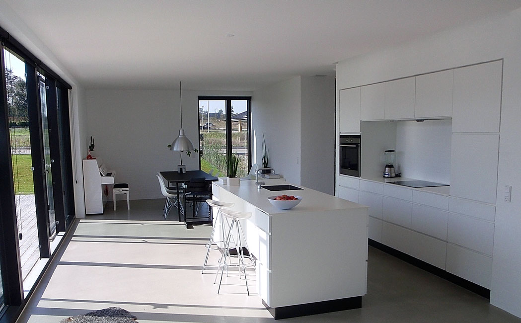 Bonnelycke mdd designed private home with combined modern white kitchen including kitchen wall and kitchen island, and a simple decorated living room with modern furniture.