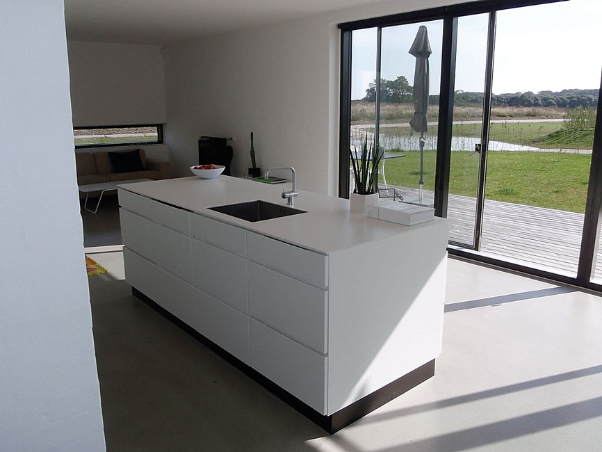 Bonnelycke mdd interior designed private home with modern white kitchen and a view to nature through big terrace doors, done by Bonnelycke. mdd