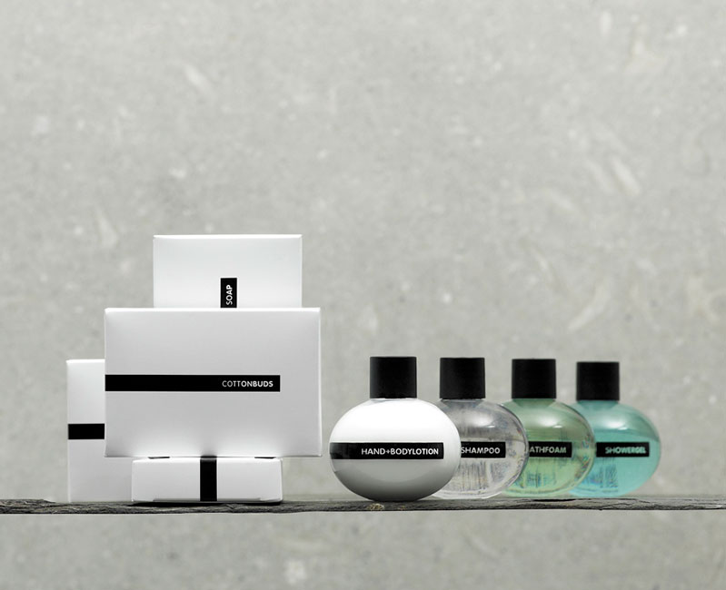 Ball guest amenities showing four glossy white rectangular paper boxes containing cotton buds, cotton pads, bath crystals and soap, and four transparent ball shaped bottles with black caps containing shampoo, bath foam, shower gel and lotion - graphics by Bonnelycke mdd