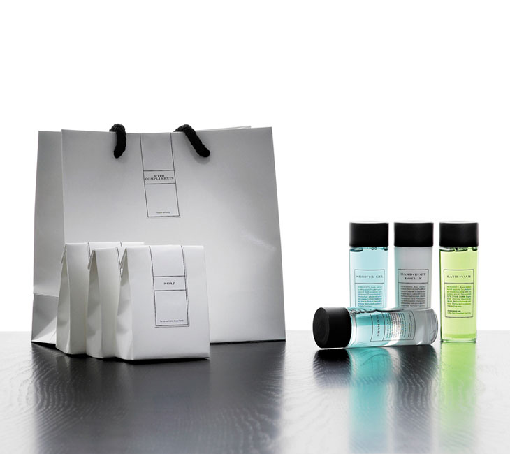 Conic guest amenities showing a big labelled glossy white conic paper bag with textile handles, three smaller conic bags containing soap, cotton buds, cotton pads, and four transparent conic bottles with black caps containing shampoo, bath foam, shower gel and lotion - graphics by Bonnelycke mdd