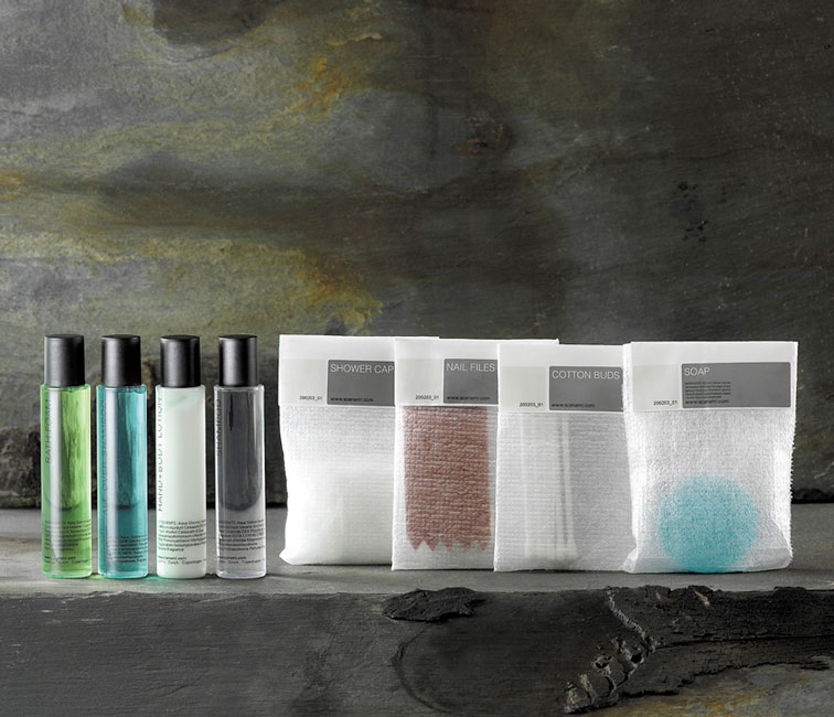 Cylindric guest amenities showing four transparent cylindrical bottles with black caps containing shower gel, bath foam, lotion and shampoo, and three labelled rectangular foam bags containing shower cap, nail files, cotton buds and soap - graphics by Bonnelycke mdd