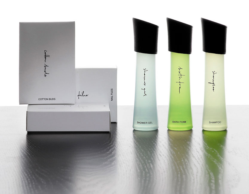 Feminine guest amenities showing three rectangular glossy white paper boxes containing cotton buds, cotton pads and nail files, and three semi-transparent cylindrical bottles with skewed black caps containing shower gel, bath foam and shampoo - graphics by Bonnelycke mdd