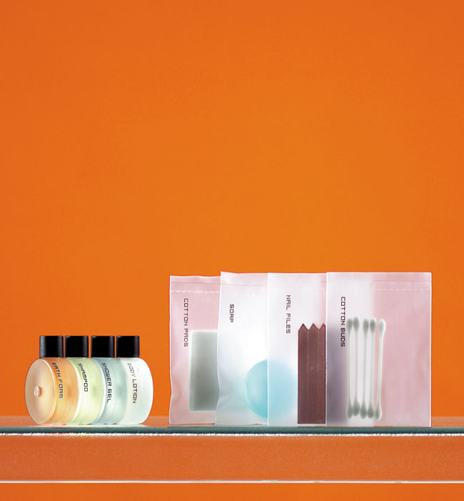 HeShe guest amenities showing four semi-transparent round connecting bottles with black caps containing bath foam, shampoo, shower gel and body lotion, and four heat sealed rectangular semi-transparent bags containing cotton pads, soap, nail files and cotton pads - graphics by Bonnelycke mdd