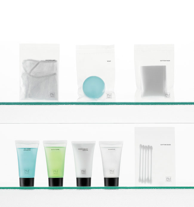 Illi guest amenities showing four semi-transparent heat sealed semi-transparent bags containing shower cap, soap, cotton pads and cotton buds, and four semi-transparent tubes and caps containing all over shampoo, bath foam, lotion and shampoo - graphics by Bonnelycke mdd