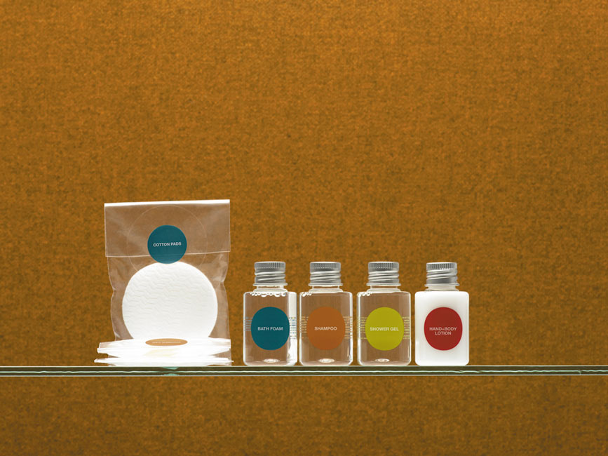 More guest amenities showing four transparent cylindrical bottles with metal caps containing bath foam, shampoo, shower gel and lotion, and three rectangular transparent bags sealed by round labels containing cotton pads and cotton buds among others - graphic print by Bonnelycke mdd