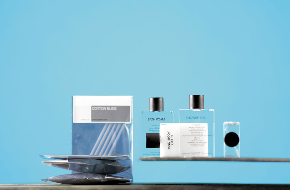 Square guest amenities showing transparent square bottles with black caps containing shower gel and shampoo among others, and four labelled rectangular metallic bags containing cotton buds among others - graphics by Bonnelycke mdd