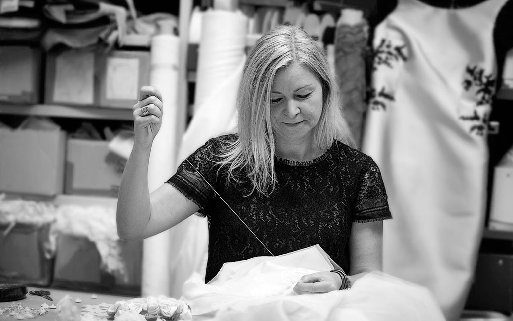 Talanted tailor Marianne Carøe adding hand sewn details to one of her wedding dress designs in her workshop