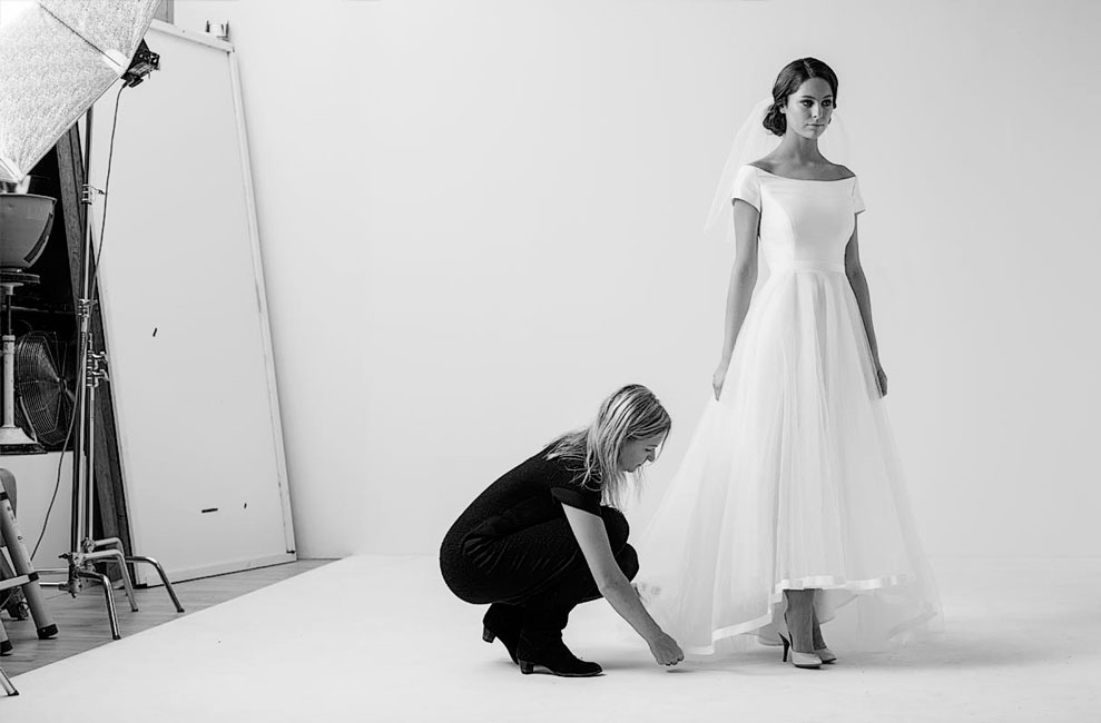 Talanted tailor Marianne Carøe finalising the details of a wedding dress on a beautiful bride