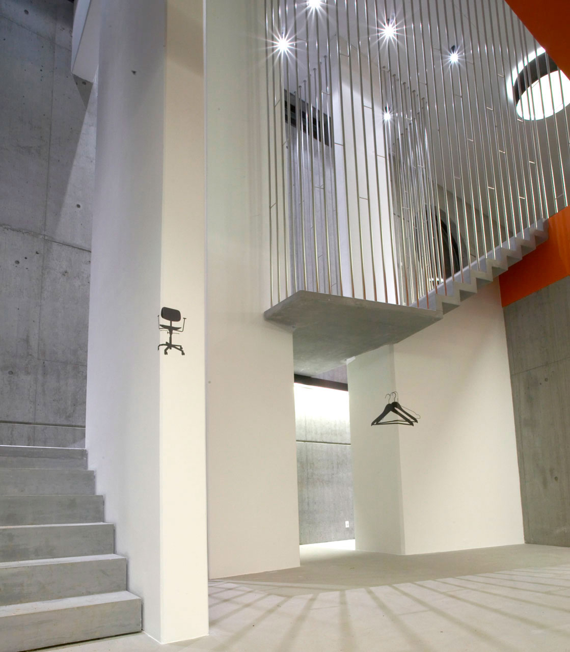 Bellinger House hall, bespoke black graphic foil on walls, concrete staircase with polished stainless steel banisters.