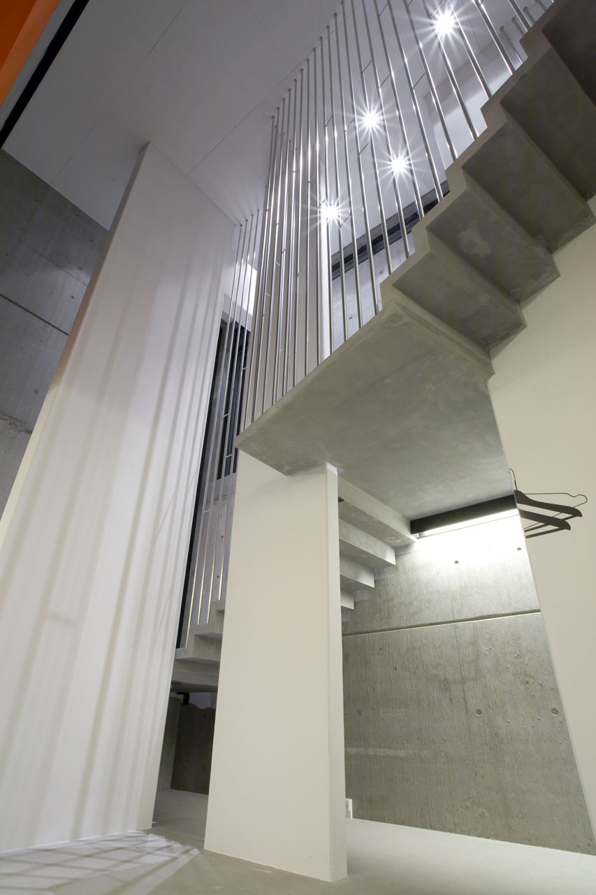 Bellinger House hall, concrete staircase with polished stainless steel banisters - view from ground floor to first floor.