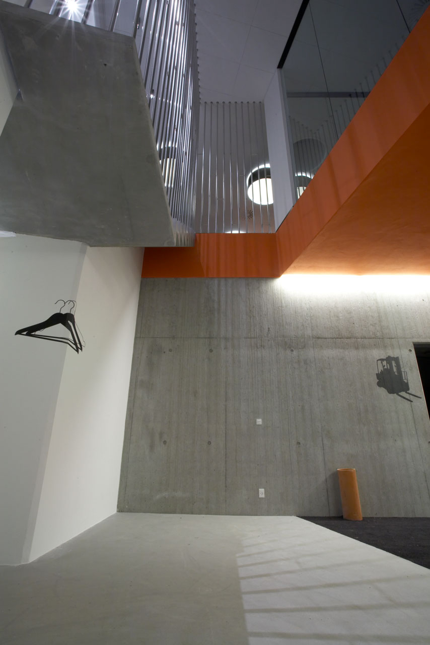Bellinger House hall, orange mid ceiling, bespoke black graphic foil on walls, concrete staircase with polished stainless steel banisters.