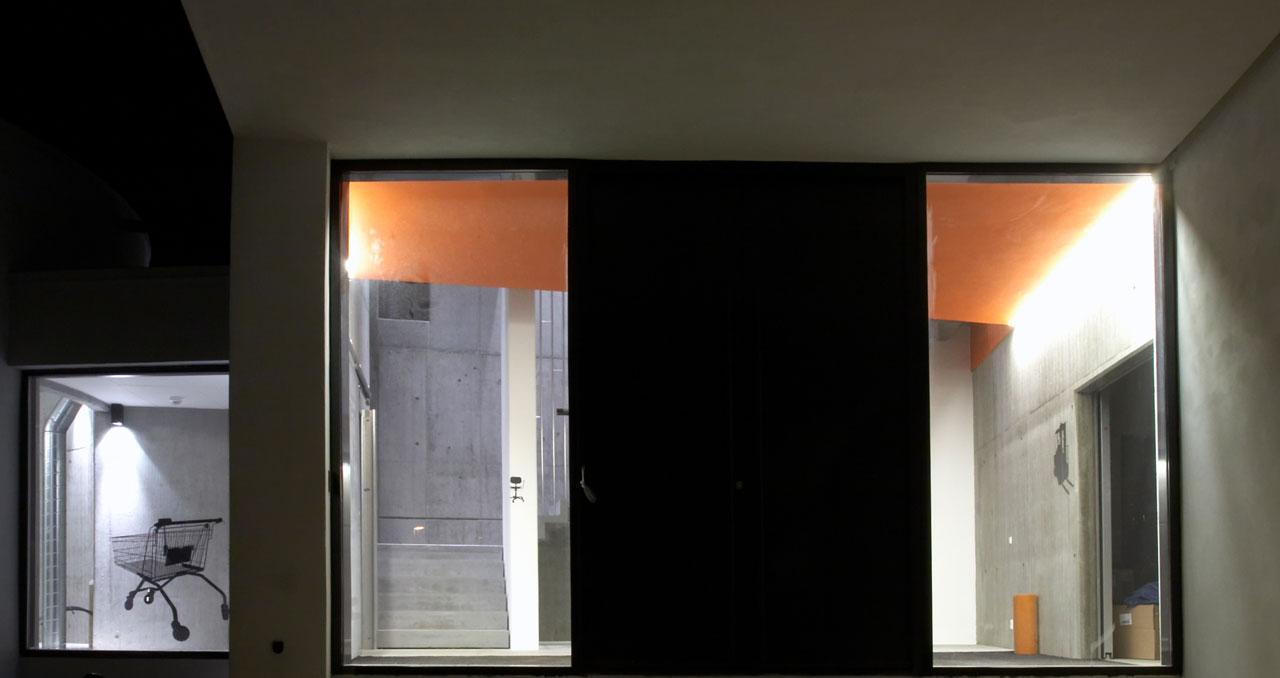Bellinger House entrance, black doors, orange ceiling and concrete staircase.