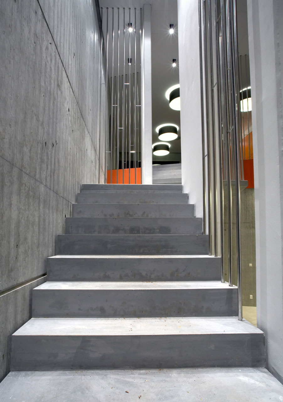 Bellinger House concrete staircase with polished stainless steel banisters.