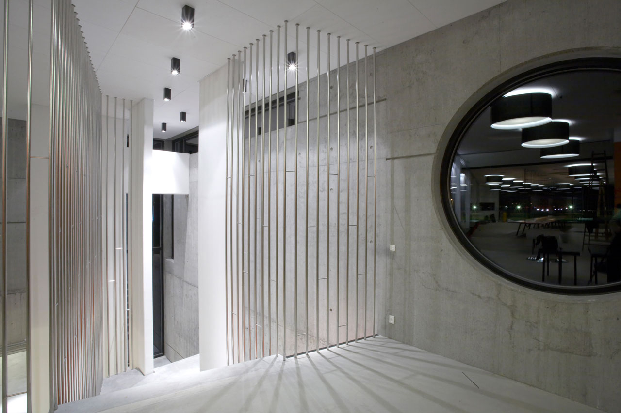 Bellinger House concrete staircase with polished stainless steel banisters and concrete wall with round window.