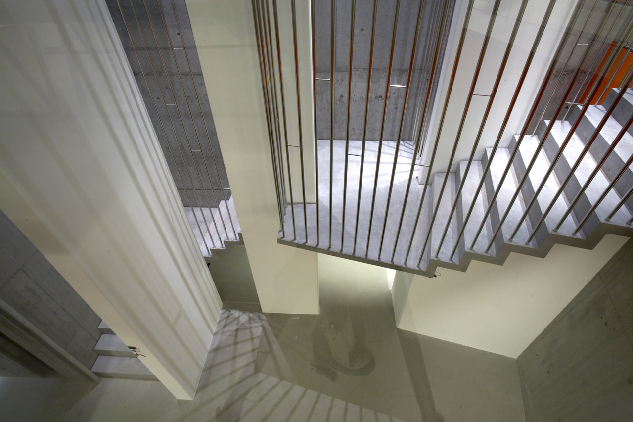 Bellinger House concrete staircase with polished stainless steel banisters - view from first floor to ground floor.