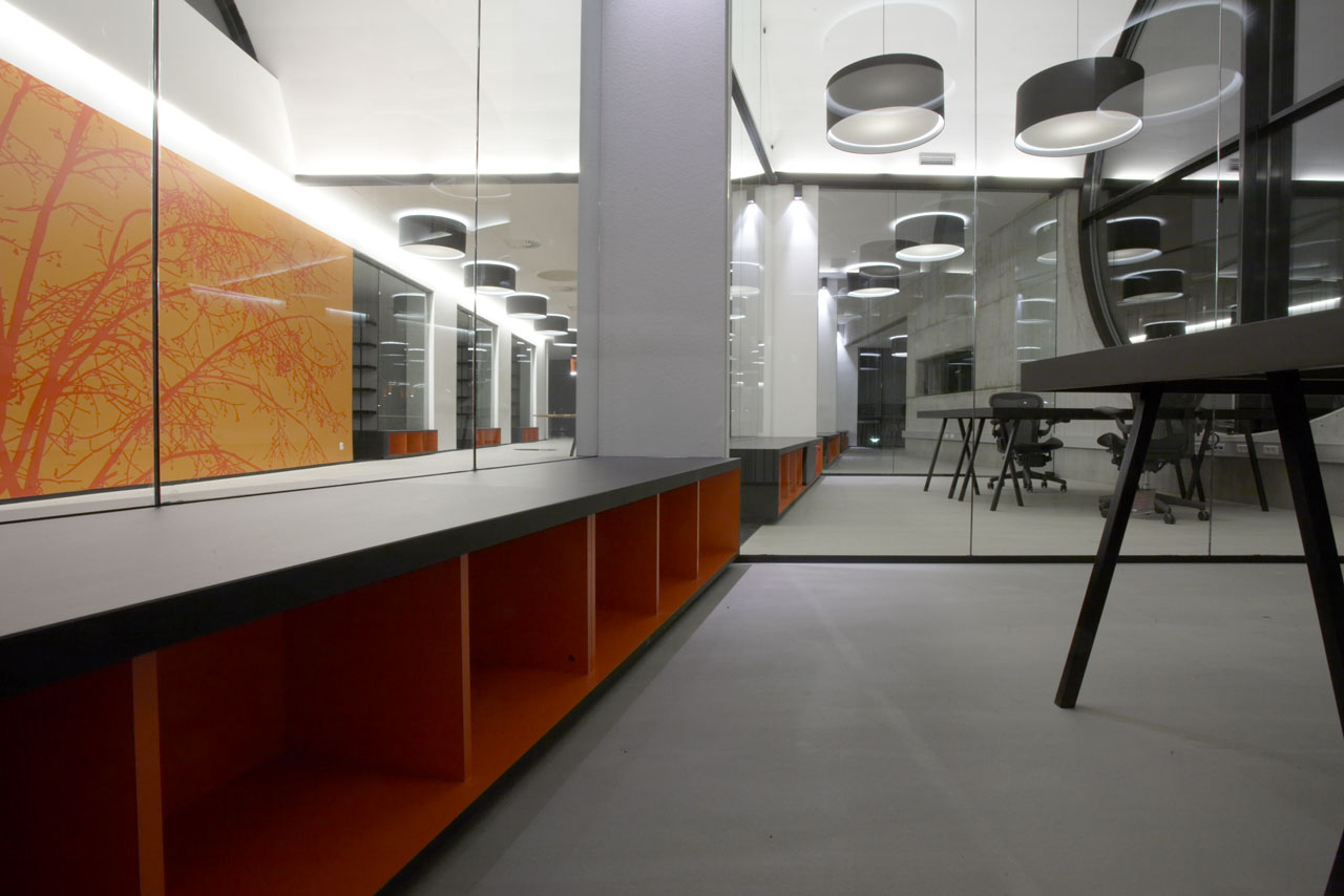 Bellinger House office, bespoke double-sided storage cabinet going through the office glass walls at the bottom, black office table and chairs, large black and white ceiling lamps and wall with bespoke orange and red graphic wallpaper.