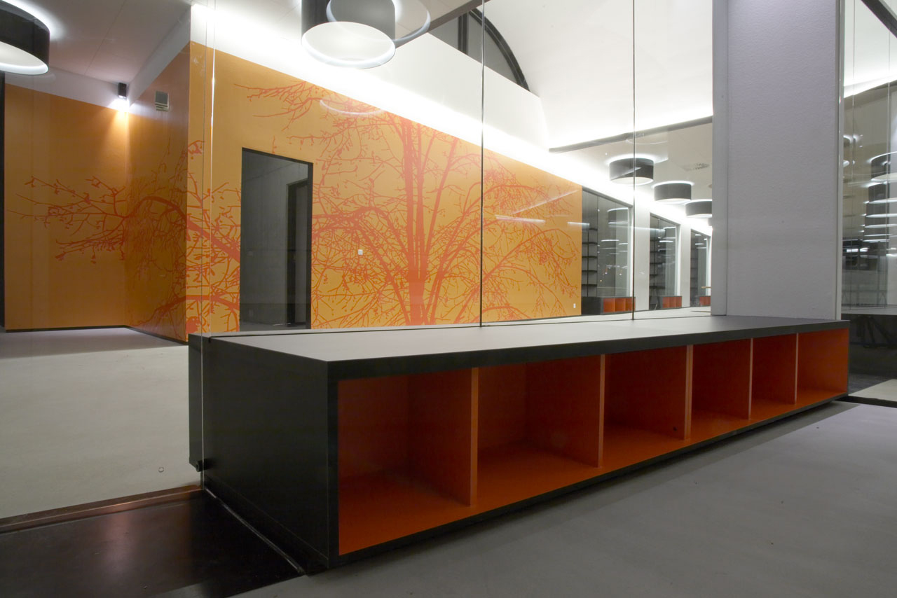 Bellinger House office, bespoke double-sided storage cabinet going through the office glass walls at the bottom, wall with bespoke orange and red graphic wallpaper.