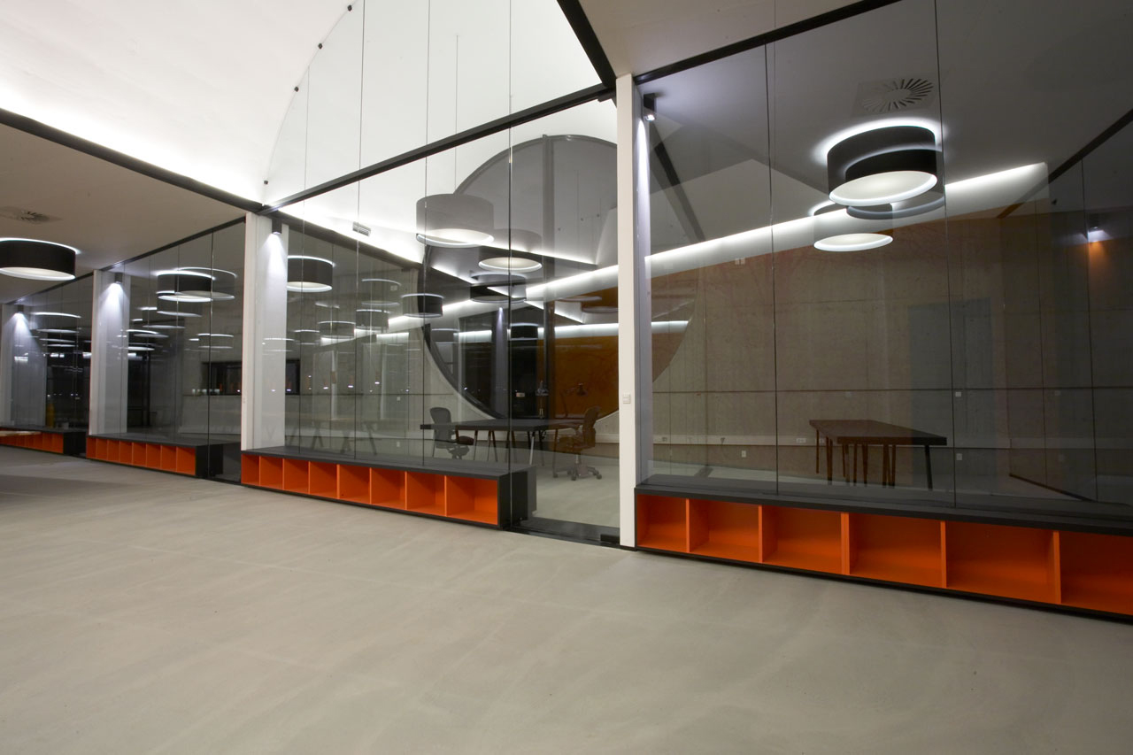 Bellinger House glass arch, bespoke double-sided storage cabinet going through the office glass walls at the bottom, black office tables and chairs and large black and white ceiling lamps.