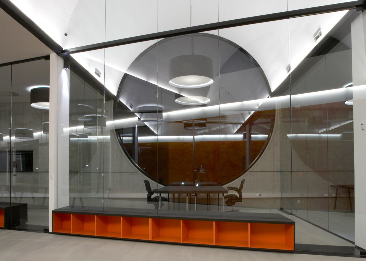 Bellinger House offices, bespoke double-sided storage cabinet going through the office glass walls at the bottom, black office tables and chairs and large black and white ceiling lamps.