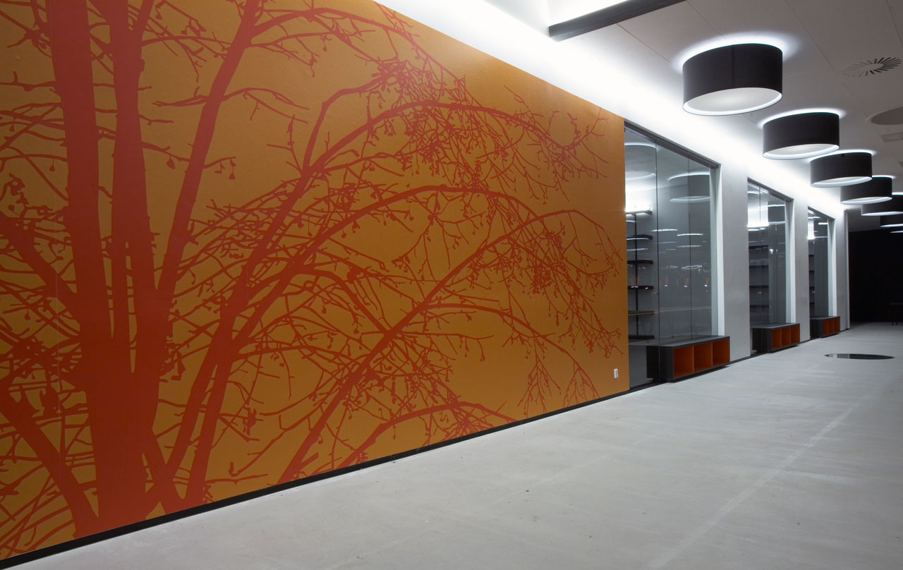 Bellinger House, wall with bespoke orange and red graphic wallpaper, large black and white ceiling lamps and bespoke double-sided storage cabinet going through the office glass walls at the bottom.