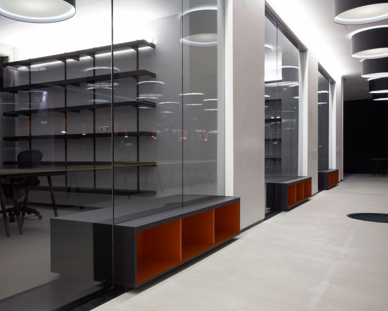 Bellinger House offices, with black office tables and chairs, black shelves, large black and white ceiling lamps and bespoke double-sided storage cabinet going through the office glass walls at the bottom.