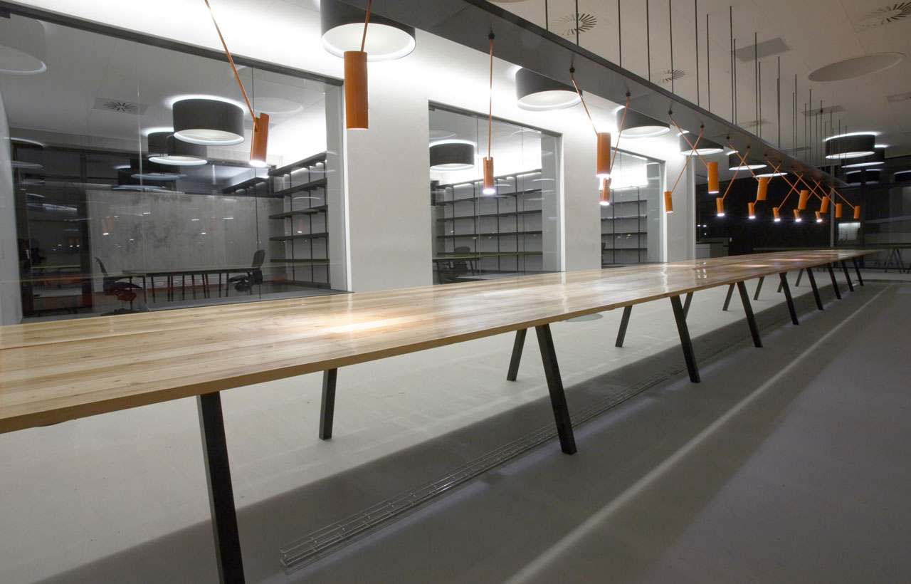 Bellinger House, long wooden office table for multiple employee stations, orange MIB customised pendants, large black and white ceiling lamps and bespoke double-sided storage cabinet going through the office glass walls at the bottom.