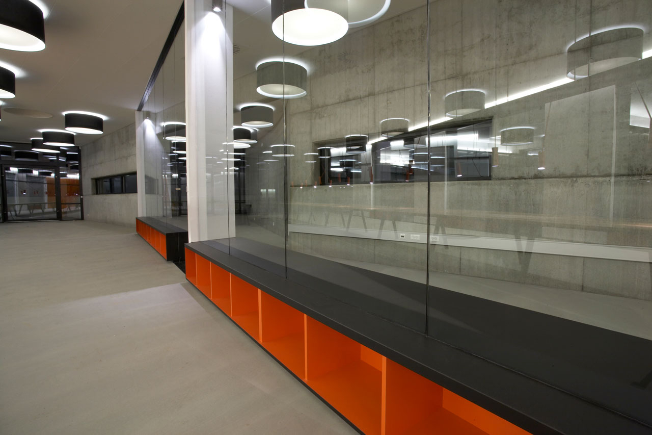 Bellinger House, bespoke double-sided storage cabinet going through the office glass walls at the bottom.