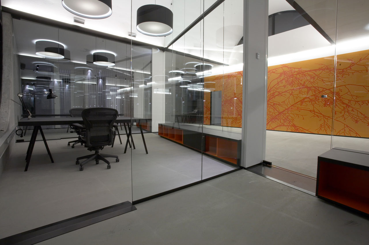 Bellinger House office, black office tables and chairs, bespoke double-sided storage cabinet going through the office glass walls at the bottom, wall with bespoke orange and red graphic wallpaper.