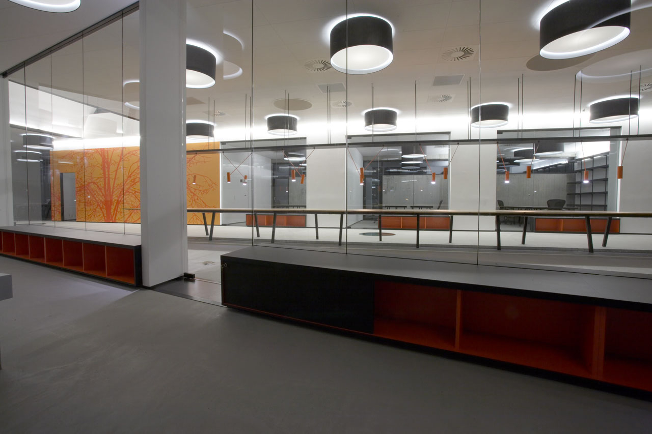 Bellinger House office, bespoke double-sided storage cabinet going through the office glass walls at the bottom, long wooden office table for multiple employee stations, orange MIB customised pendants, large black and white ceiling lamps, wall with bespoke orange and red graphic wallpaper.