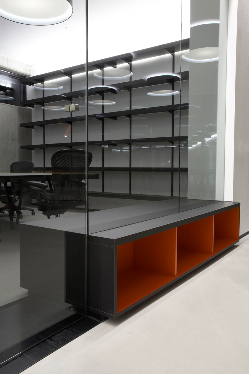 Bellinger House office, bespoke double-sided storage cabinet going through the office glass walls at the bottom, black office tables and chairs, black shelves and large black and white ceiling lamps.