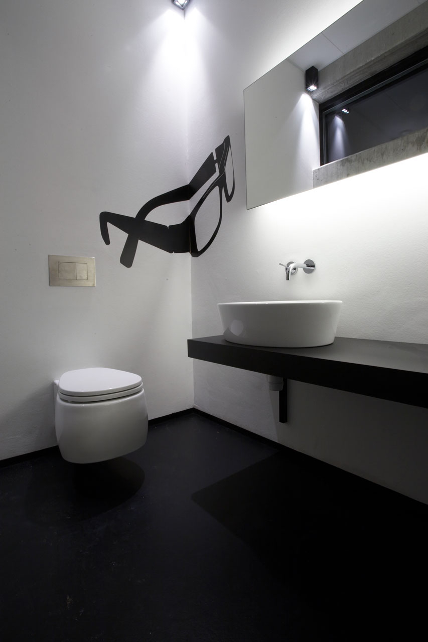 Bellinger House bathroom, porcelain toilet, bespoke black graphic foil glasses on the wall, bespoke black bathroom furniture, porcelain sink and rectangular mirror.