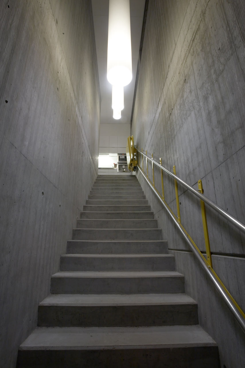 Bellinger House concrete staircase with yellow lift - view from ground floor to first floor.